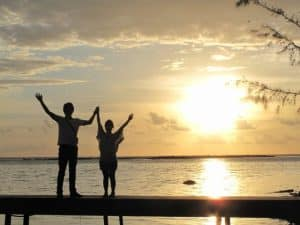 夕陽に向かって万歳するカップル