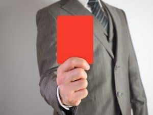 レッドカードを持つスーツ姿の男性