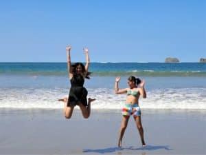 砂浜で飛び跳ねる女性