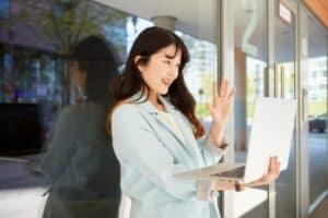 女性がパソコンに手を振る画像